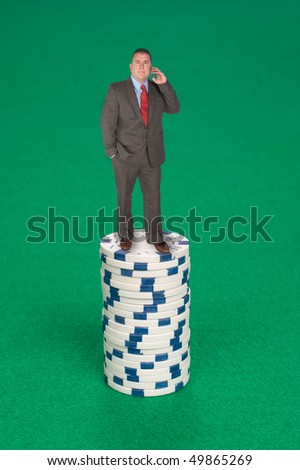 A man stands on a stack of poker chips calling in his bet.