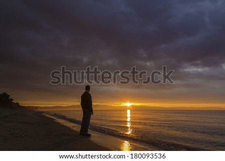 A man stands on the beach watching the sunrise over mountains by the sea. Tuscany, Italy / Man looking at sunrise - stock photo