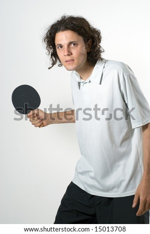 A man, stands seriously, holding a ping pong paddle, getting ready to hit the ball. Vertically framed shot. - stock photo