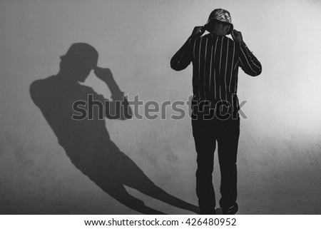 A man stands with his back facing the camera, with his shadow beside him - stock photo