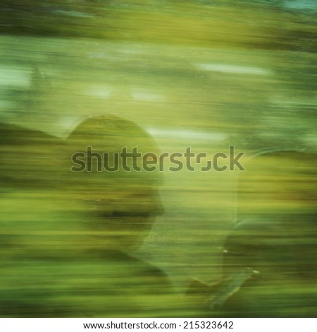 A man staring at his smartphone. Reflection in the moving train window. A man playing games on his mobile phone. - stock photo