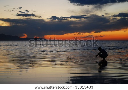 A man staring into his reflection during an amazing sunset - stock photo