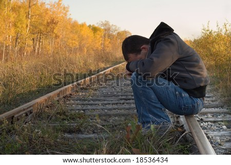 A man suffering from severe depression, sitting on some train tracks - stock photo