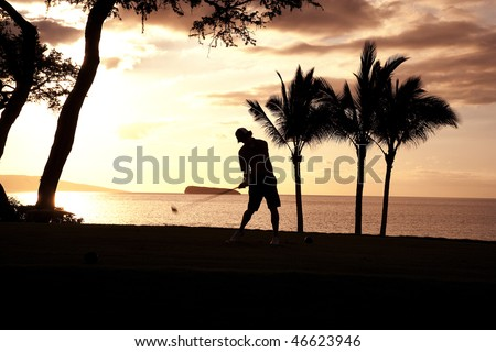 A man swings his golf club amidst a tropical setting. Palm trees and the ocean are in the background. Horizontal shot. - stock photo