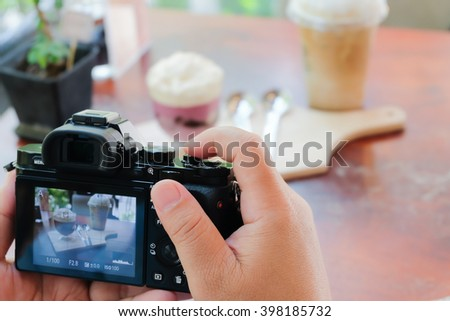 A man taking a picture of a coffee cup with his camera while sitting at a coffee shop.
