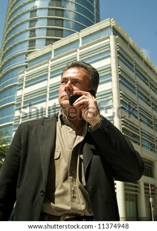 A man talking on a cell phone with large buildings in the back ground. - stock photo