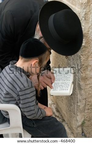 A man teaching a boy scripture. - stock photo
