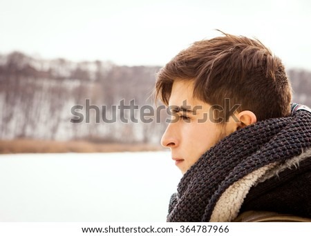 a man traveling in a cold winter day, looking at the river