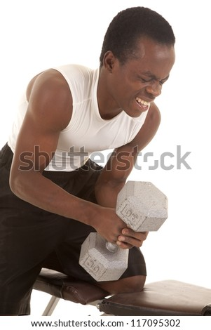 A man trying to lift a heavy weight with a painful expression on his face. - stock photo