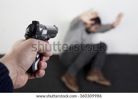 A man under the gun threat - stock photo