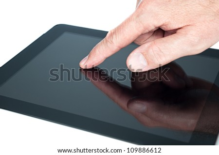 A man uses a touch pad tablet to gain wireless Internet access. - stock photo