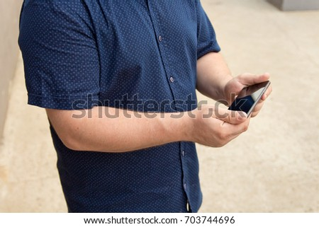 A man uses his phone. Man in blue shirt with smart phone on hand with copy space