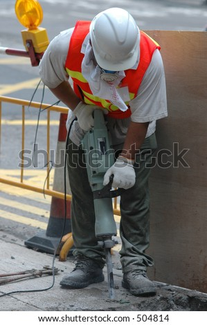 a man using a jackhammer for road works - stock photo