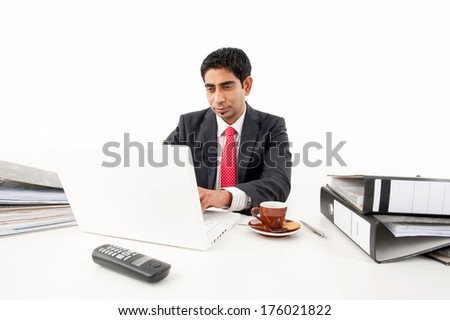 A man using a laptop with a cup and saucer and binders on the table.