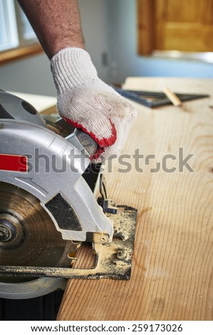 a man using a saw to cut a piece of wood - stock photo
