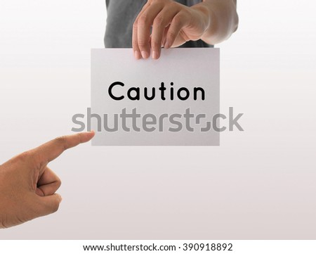a man using hand holding the white paper with text caution