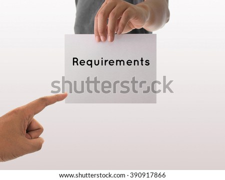 a man using hand holding the white paper with text requirements