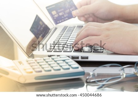 A man using his computer laptop and holding credit card intent to shopping online concept, digital business or e-commerce with calculator and glasses. warm tone. - stock photo
