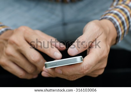 A man using mobile smart phone in relax time, close up.