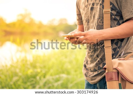 A man using mobile smart phone side lake. - stock photo