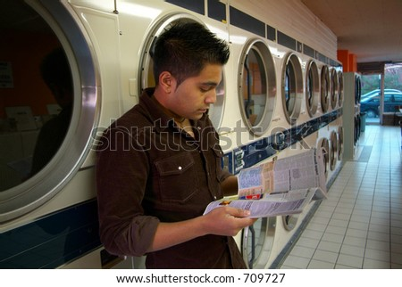 A man waiting for his clothes to dry at a local laundromat. - stock photo