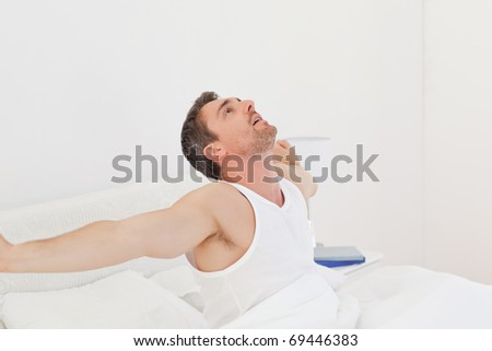 A man waking up in his bedroom - stock photo