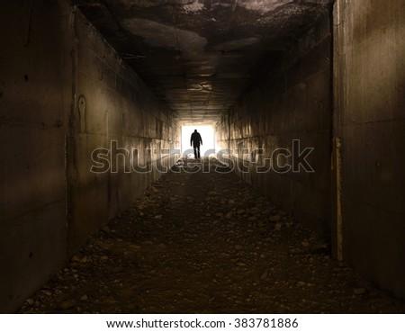 A man walking alone in the dark tunnel - stock photo