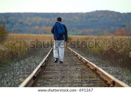 A man walking along train tracks - stock photo