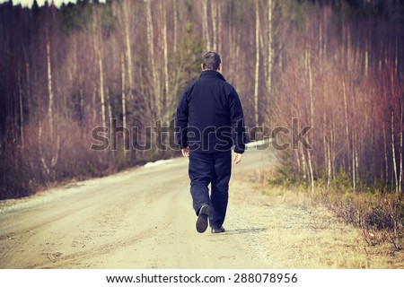 A man walking on a silent road. Image has a strong instagram and vintage effect. - stock photo