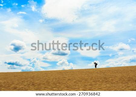 A man walking on sand desert - stock photo