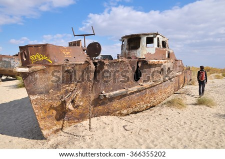 A man walks next to the ship middle of a desert. - stock photo