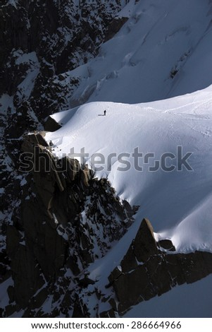 A man walks to edge of steep mountain in Mont Blanc massif in France - stock photo