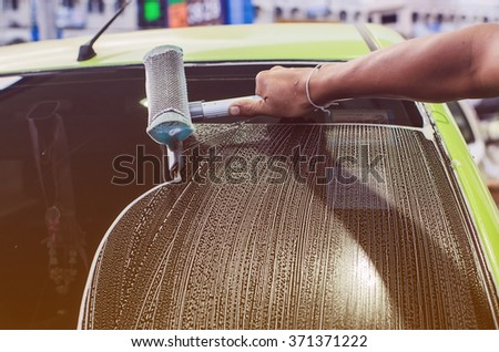 A man washing a car's window using a rag and a spray - stock photo