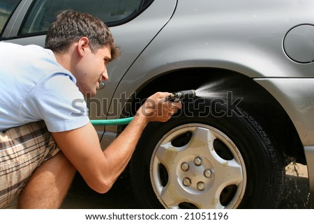 A man washing his car.  He is using a hose to wash the tires. Horizontally framed shot. - stock photo
