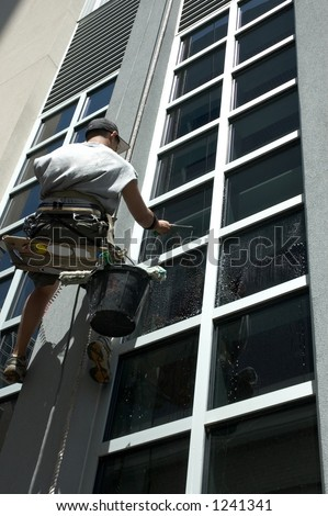 A man washing the windows of a skyscraper.