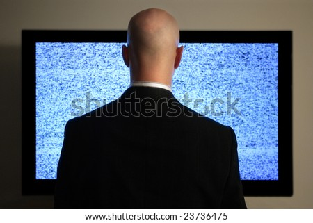 A man watching a blank or static screen of his television. - stock photo