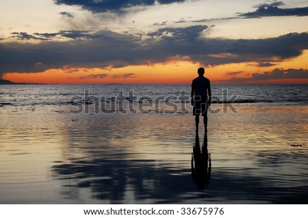 A man watching the sunset over a lake - stock photo