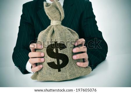 a man wearing a black suit holding a burlap money bag - stock photo