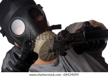 A man wearing a gas mask pointing two guns at the viewer. Shallow depth of field.  Works great for crime or warfare concepts. - stock photo