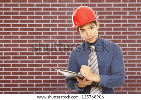 A man wearing a hardhat (against a brick wall background) - stock photo