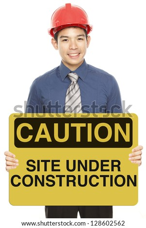 A man wearing a hardhat and holding a caution or safety sign - stock photo