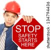 A man wearing a hardhat holding a Stop sign with a safety message (shallow depth of field)  - stock photo