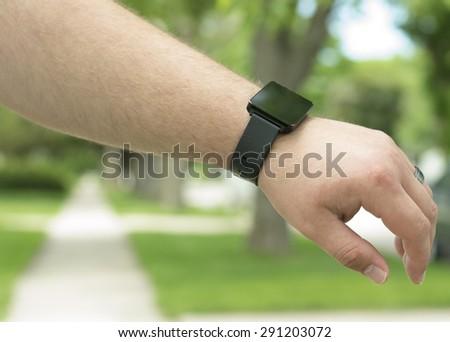 A man wearing a smar twatch outside. - stock photo