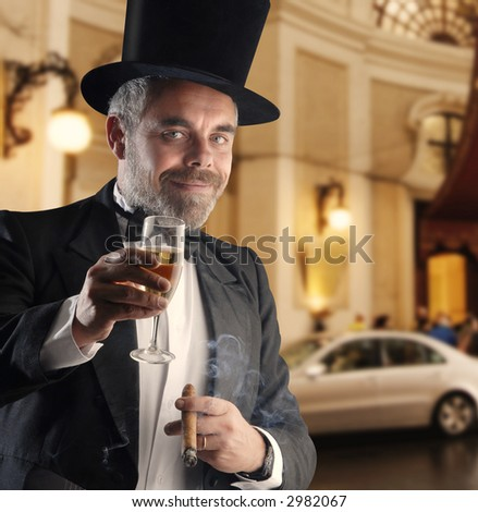 a man wearing a smoking holding a glass and cigar, against a luxury blurry background - stock photo