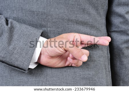 a man wearing a suit crossing his fingers in his back - stock photo