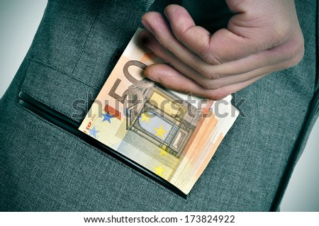 a man wearing a suit getting euro bills in the pocket of his jacket - stock photo