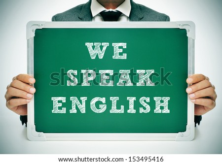 a man wearing a suit holding a chalkboard with the sentence we speak english written in it - stock photo