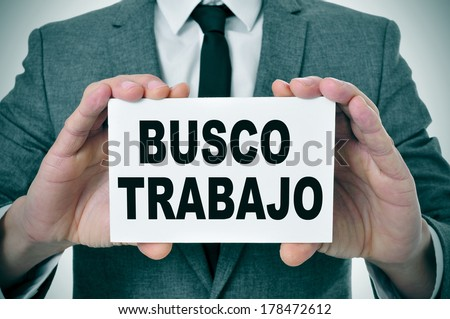a man wearing a suit holding a signboard with the text busco trabajo, looking for a job written in spanish - stock photo