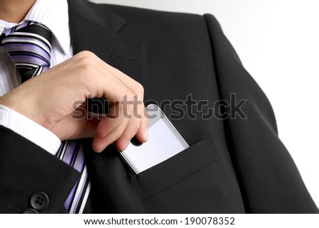 A man wearing a suit is taking out his smartphone from his coat pocket. - stock photo
