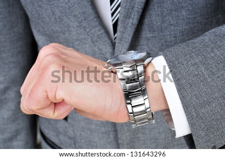 a man wearing a suit looking at his watch - stock photo